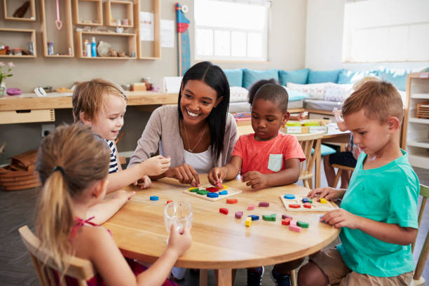teacher and pupils using wooden shapes in montessori school - preschool teacher stock pictures, royalty-free photos & images