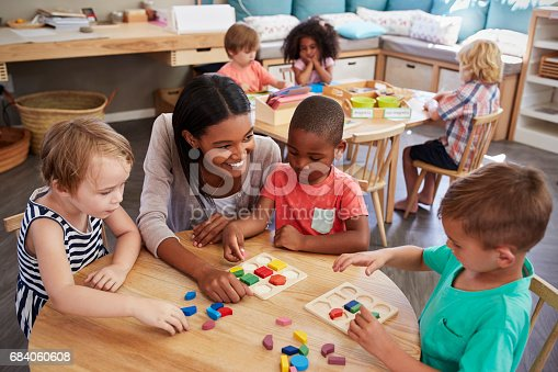 istock Teacher And Pupils Using Wooden Shapes In Montessori School 684060608