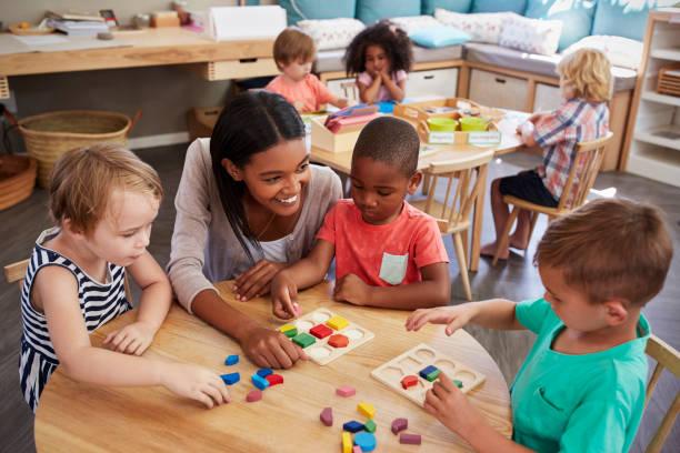 Enseignant et élèves utilisant des formes en bois dans l'école Montessori - Photo