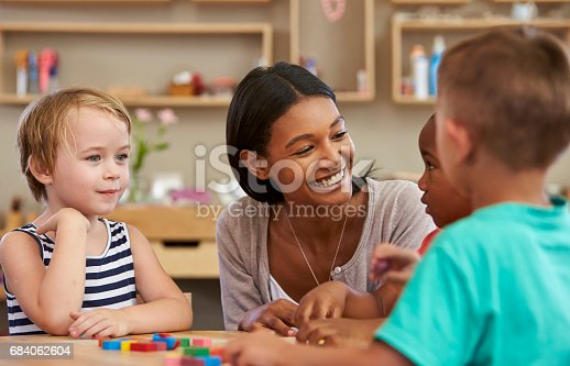 istock Teacher And Pupils Using Wooden Shapes In Montessori School 684062604