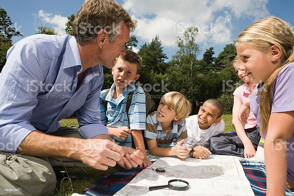 Teacher and pupils with map stock photo