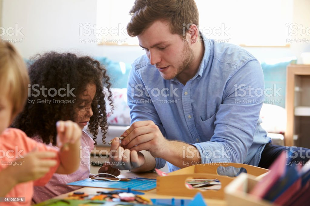 Teacher And Pupils Working At Tables In Montessori School stock photo