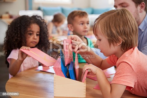 684059604 istock photo Teacher And Pupils Working With Letters In Montessori School 684056980