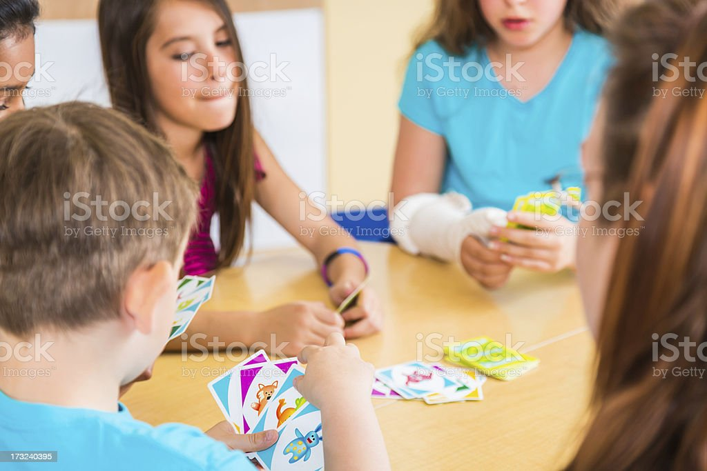 Teacher and school children playing card game in classroom. Taken on...