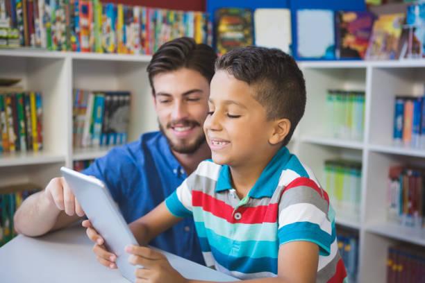 lehrer und schule kind mit digitalen tisch in bibliothek - möbel 24 online stock-fotos und bilder