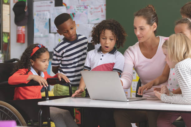Teacher and school kids discussing over laptop in classroom stock photo