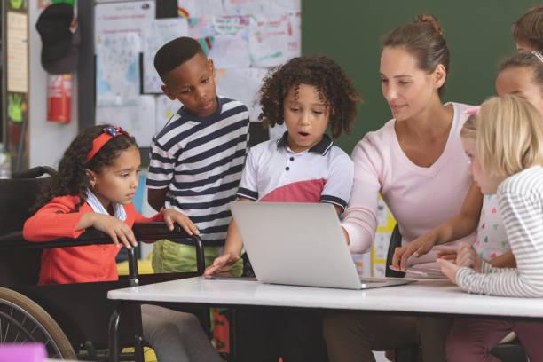 Lehrer und Schulkinder diskutieren über Laptop im Unterricht – Foto
