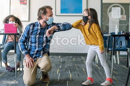A friendly male teacher greets an elementary age student with an elbow bump in school classroom during COVID-19 pandemic reopening.
