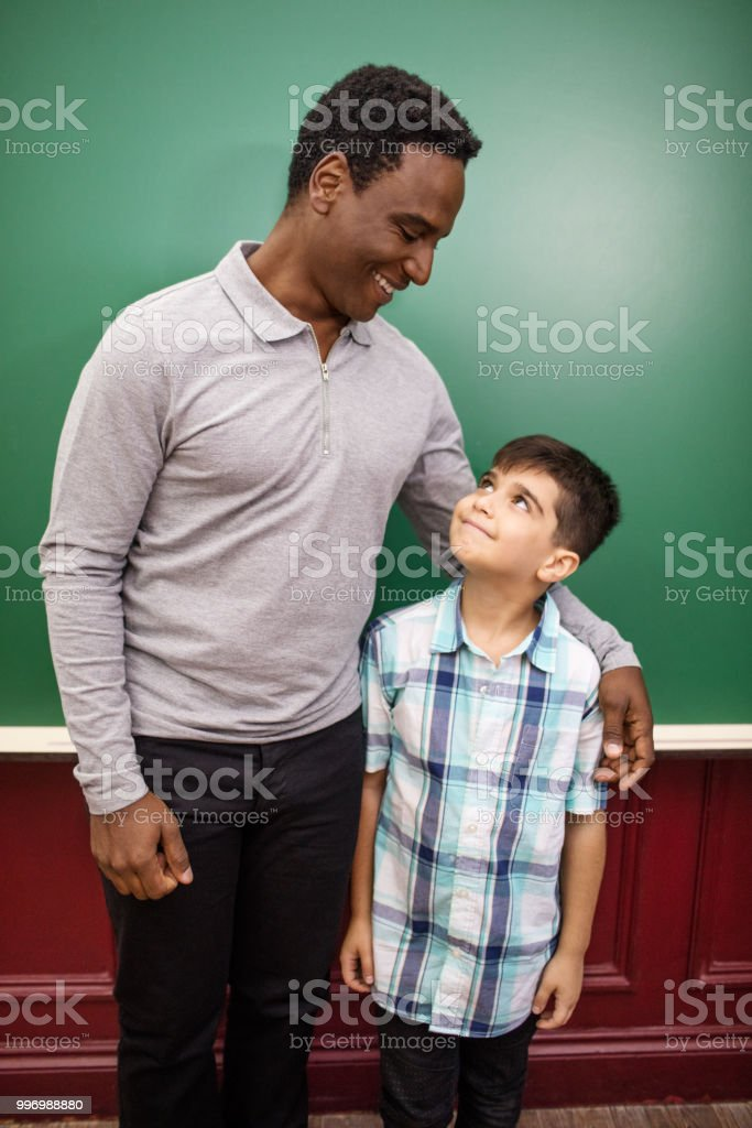 Smiling teacher and student looking at each other against blackboard....