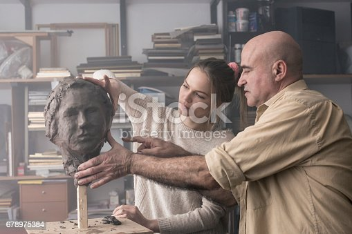 Teacher helping student sculpting clay face