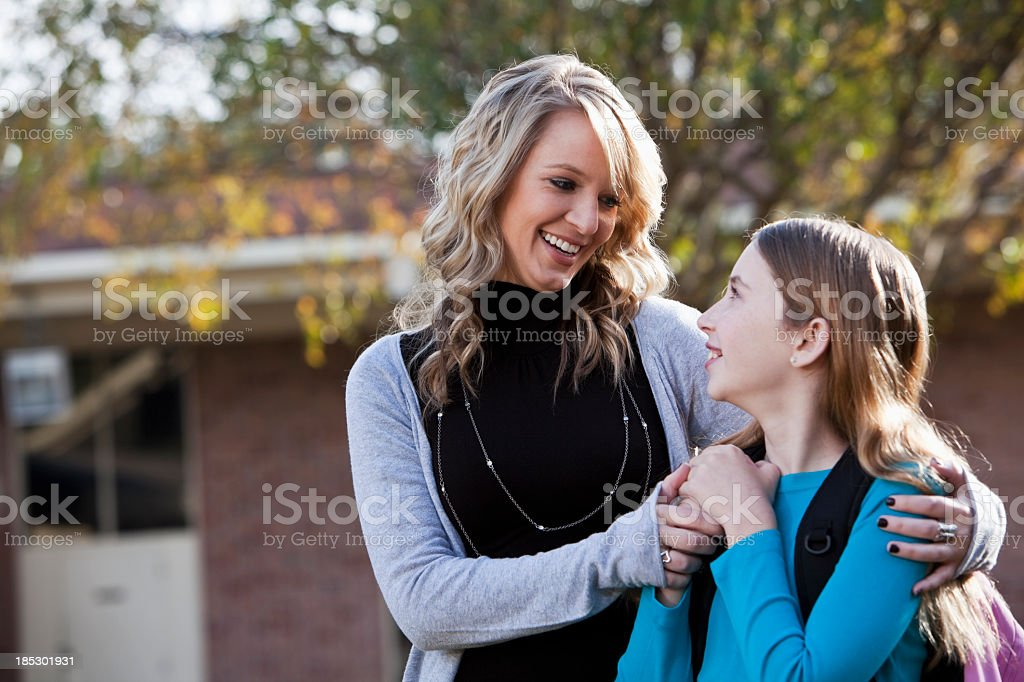 Middle school student standing with teacher outside school.