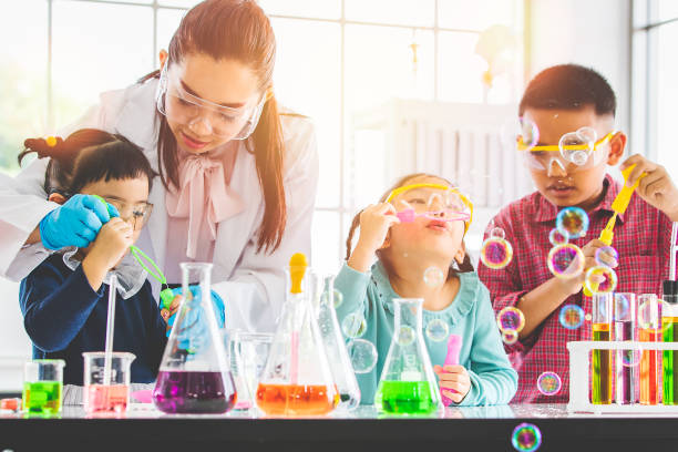 Professor e alunos soprando bolhas no laboratório. - foto de acervo