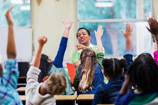An African-American teacher, a mature woman in her 40s, sitting in front of her class of elementary school students, 6 and 7 years old, reading a book. She has asked a question and all of the children are raising their hands. They are in first grade or second grade. The focus is on two of the girls.