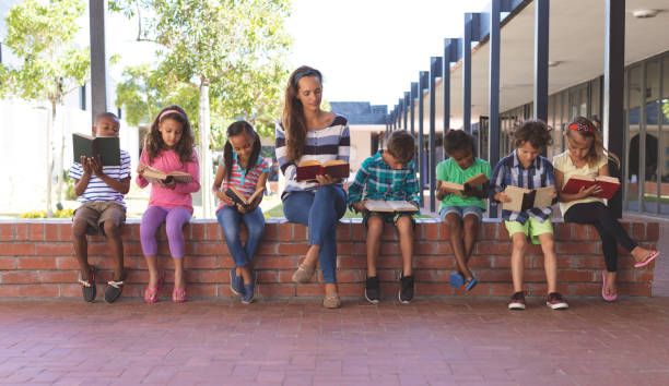 Teacher and students reading book while sitting on brick wall at corridor stock photo