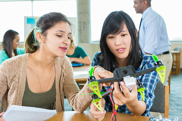 Teacher and students work on drone at STEM school - foto stock