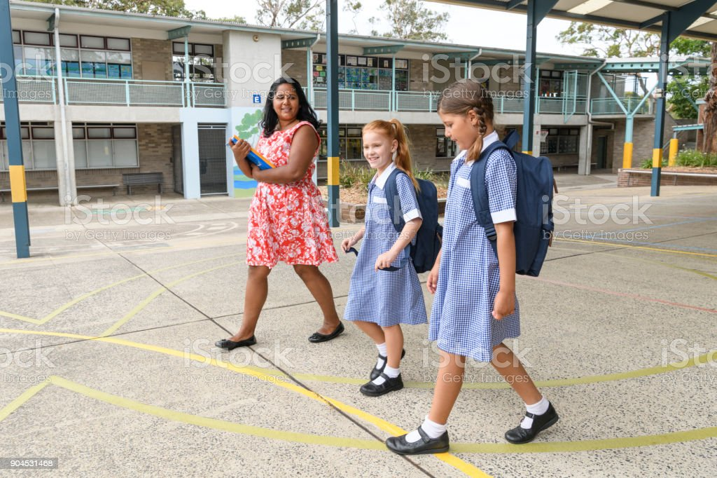 Teacher and two female pupils walking across school yard stock photo