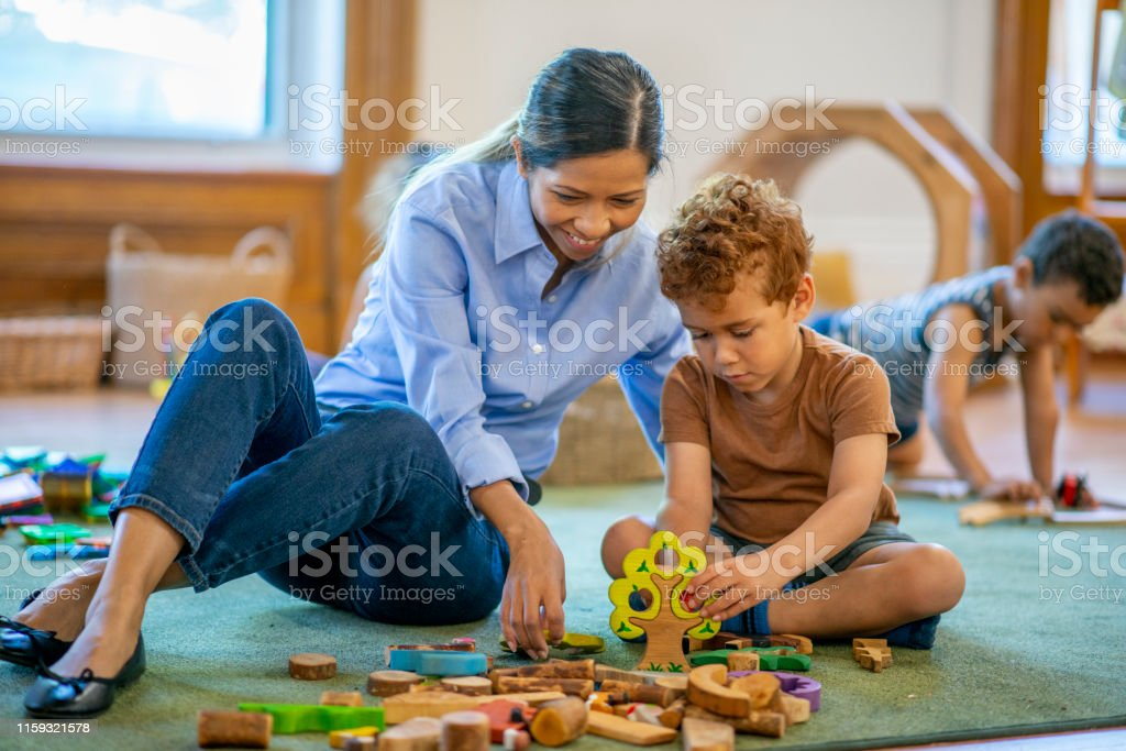 Preschool classroom student and teacher play with toys together.