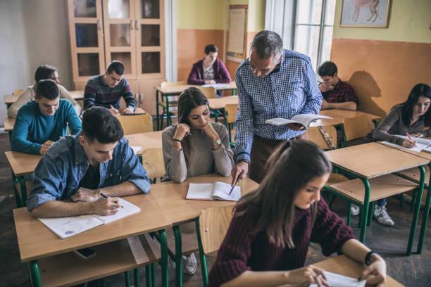 Professeur d'aider une étudiante d'étudier en classe. - Photo