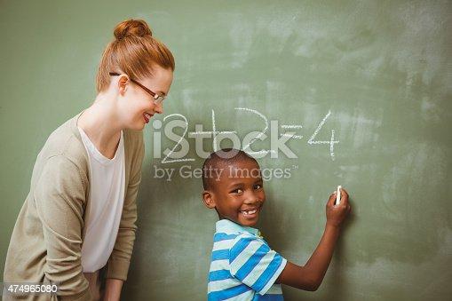 istock Teacher assisting boy to write on blackboard in classroom 474965080