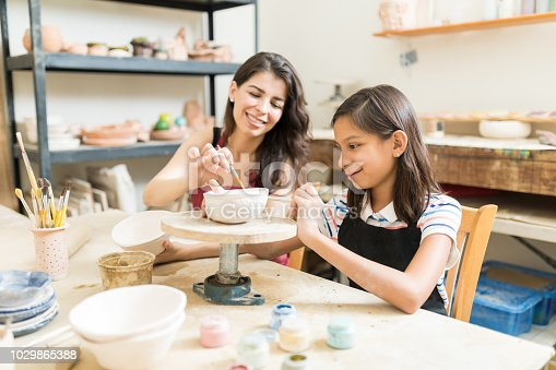 istock Teacher Assisting Girl To Unleash Her Creativity Of Pottery Painting 1029865388