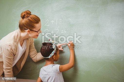istock Teacher assisting girl to write on blackboard in classroom 474964610