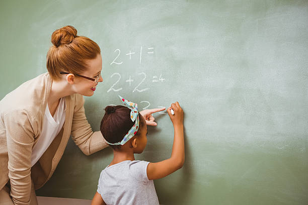 teacher assisting girl to write on blackboard in classroom - teachers day stock photos and pictures