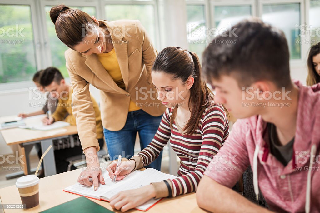 Teacher assisting her student in the classroom. stock photo