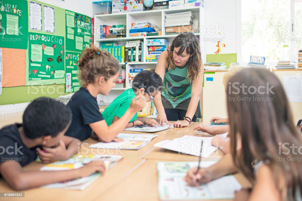 Teacher assisting school children in classroom stock photo