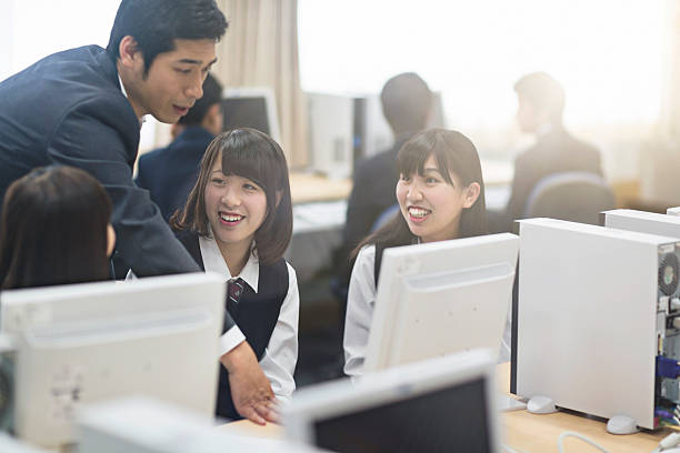 teacher assisting school girls in computer lab - 高等学校 ストックフォトと画像