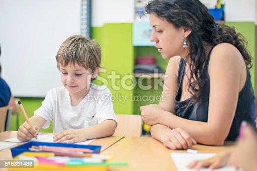 istock Teacher assisting schoolboy in drawing on papers 816391438