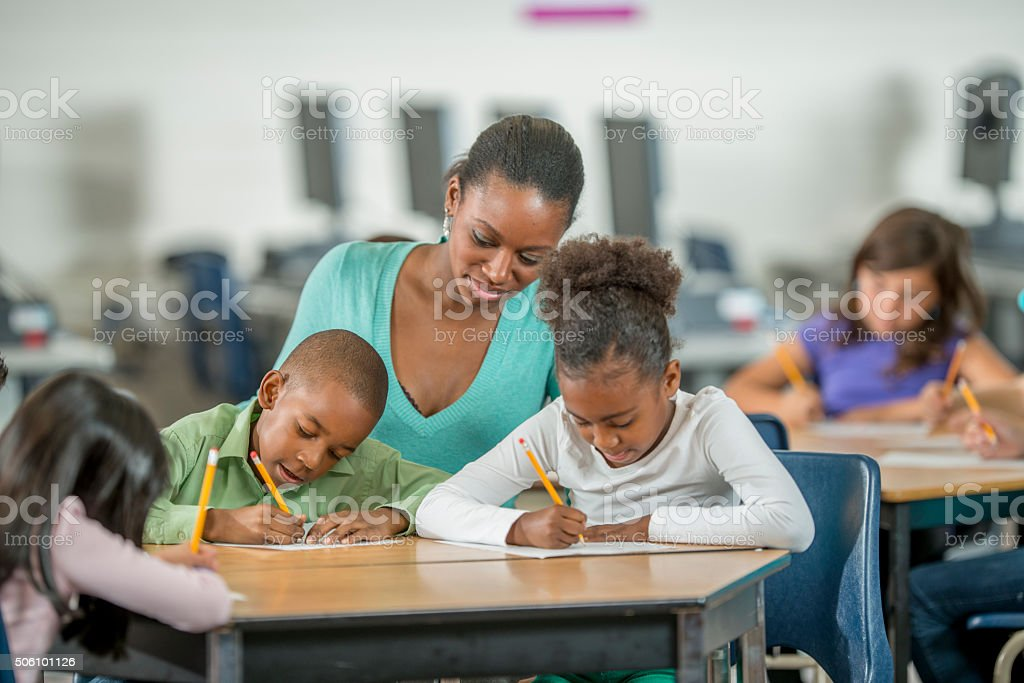 Teacher Assisting Students with Homework stock photo