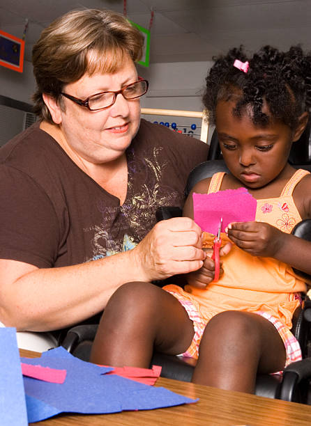 Teacher assists little girl with art project stock photo