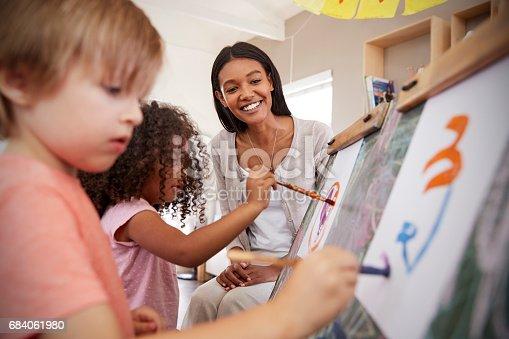 684059604 istock photo Teacher At Montessori School Helping Children in Art Class 684061980