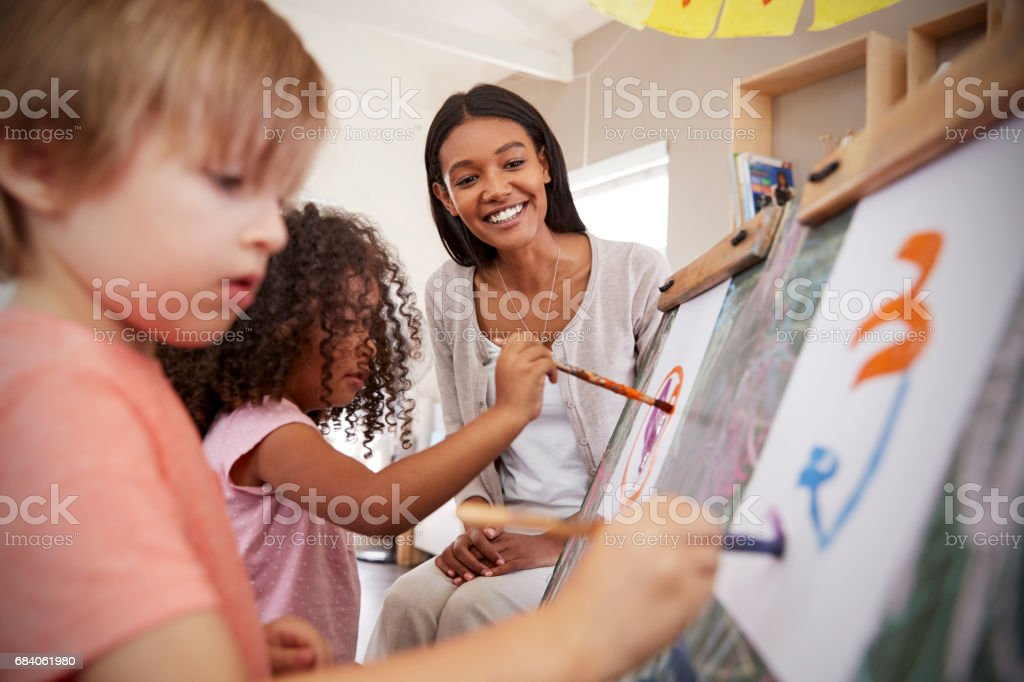 Teacher At Montessori School Helping Children in Art Class stock photo