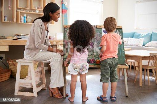 684059604 istock photo Teacher At Montessori School Helping Children in Art Class 684062006