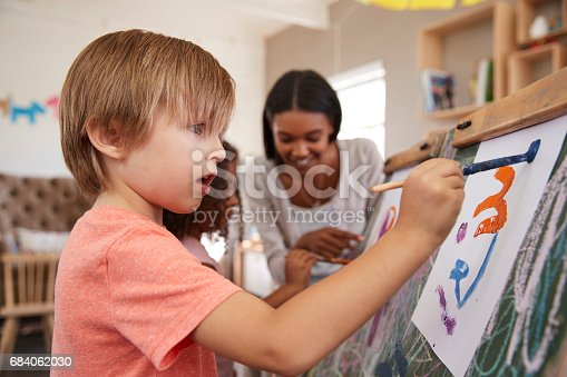 684059604 istock photo Teacher At Montessori School Helping Children in Art Class 684062030