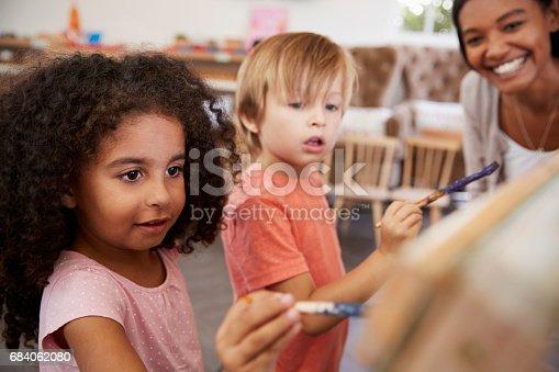 684059604 istock photo Teacher At Montessori School Helping Children in Art Class 684062080