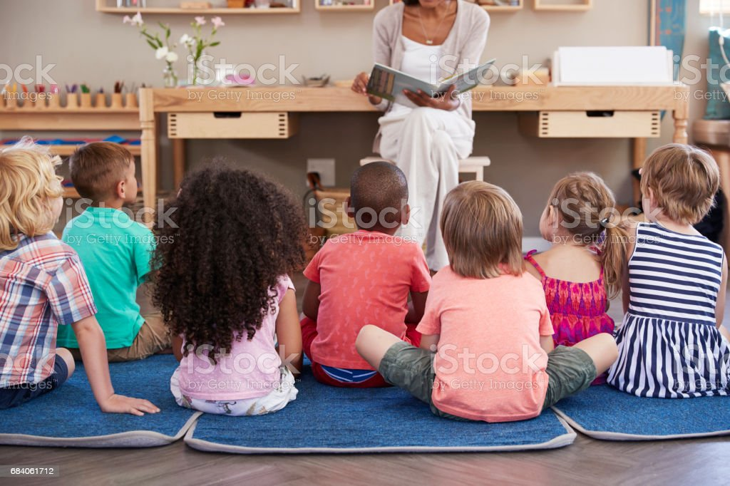 Teacher At Montessori School Reading To Children At Story Time - foto stock