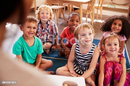 684059604 istock photo Teacher At Montessori School Reading To Children At Story Time 684061924