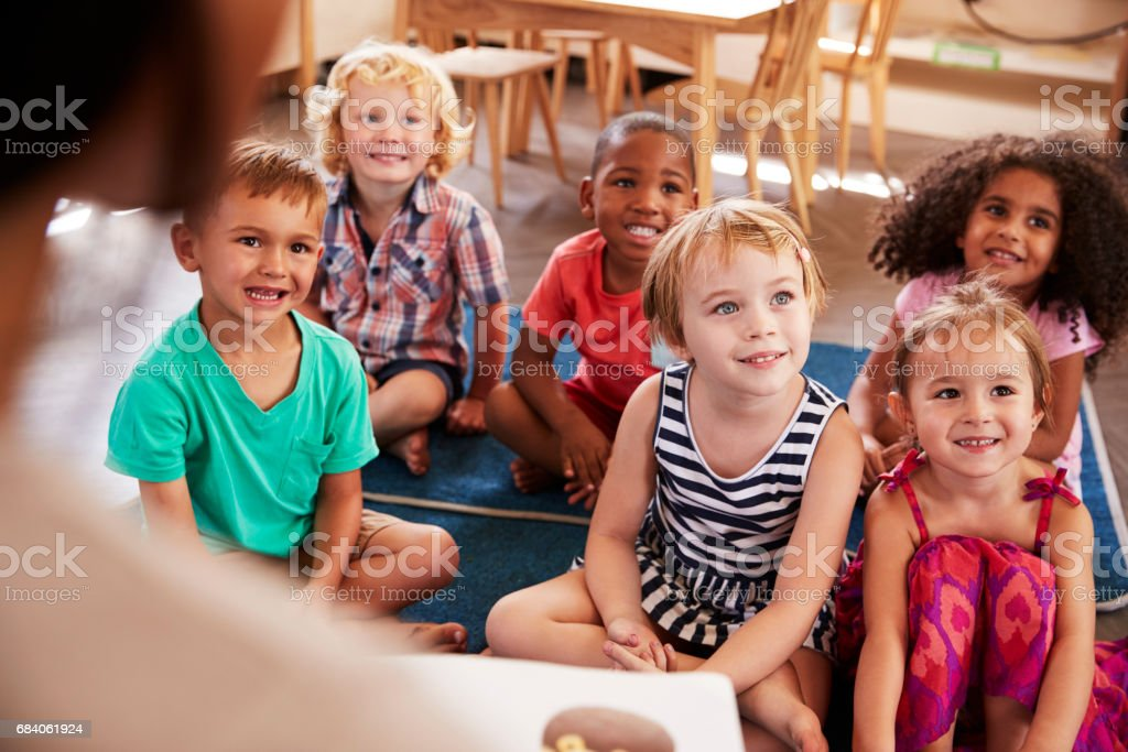 Teacher At Montessori School Reading To Children At Story Time stock photo