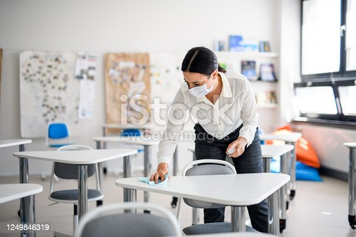 Teacher back at school after covid-19 quarantine and lockdown, disinfecting desks at break time.