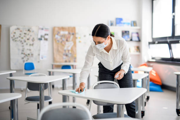 Teacher back at school after covid-19 quarantine and lockdown, disinfecting desks. stock photo