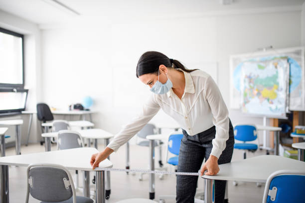 Teacher back at school after covid-19 quarantine and lockdown, measuring distance of desks. stock photo
