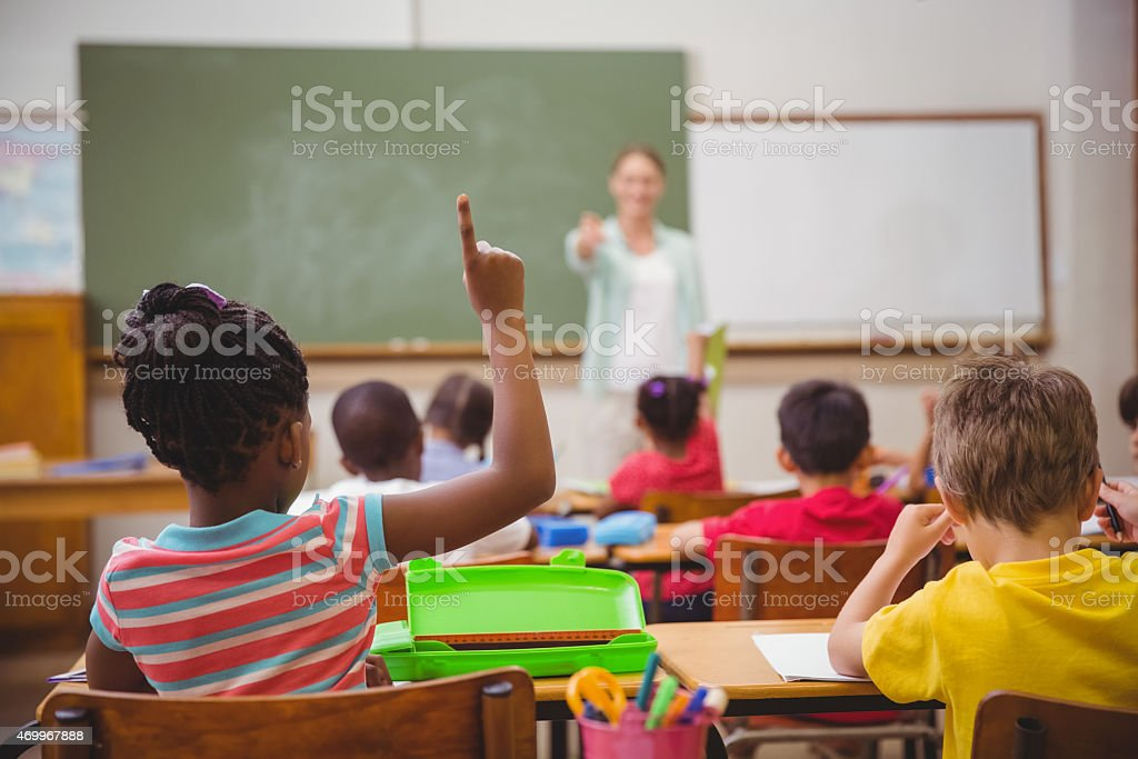 Teacher calling on student raising her hand stock photo
