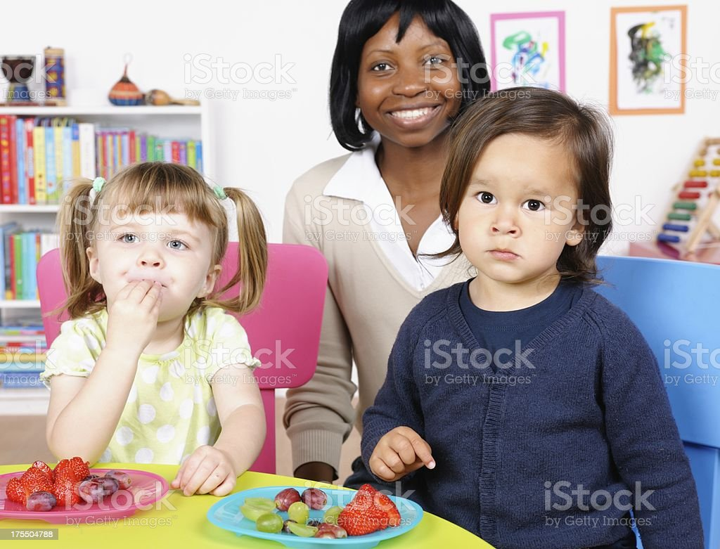 Teacher/ Carer Supervising Little Boy And Girl At Mealtime royalty-free stock photo