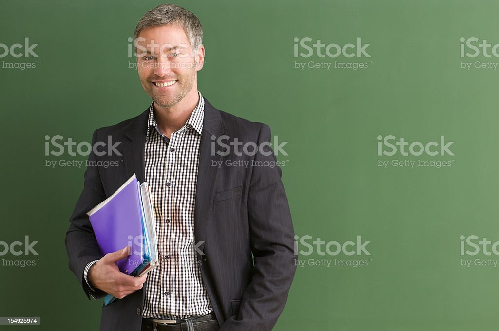 Teacher carrying books and standing by the blackboard stock photo