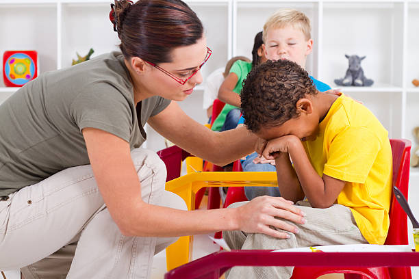teacher comforting crying boy stock photo