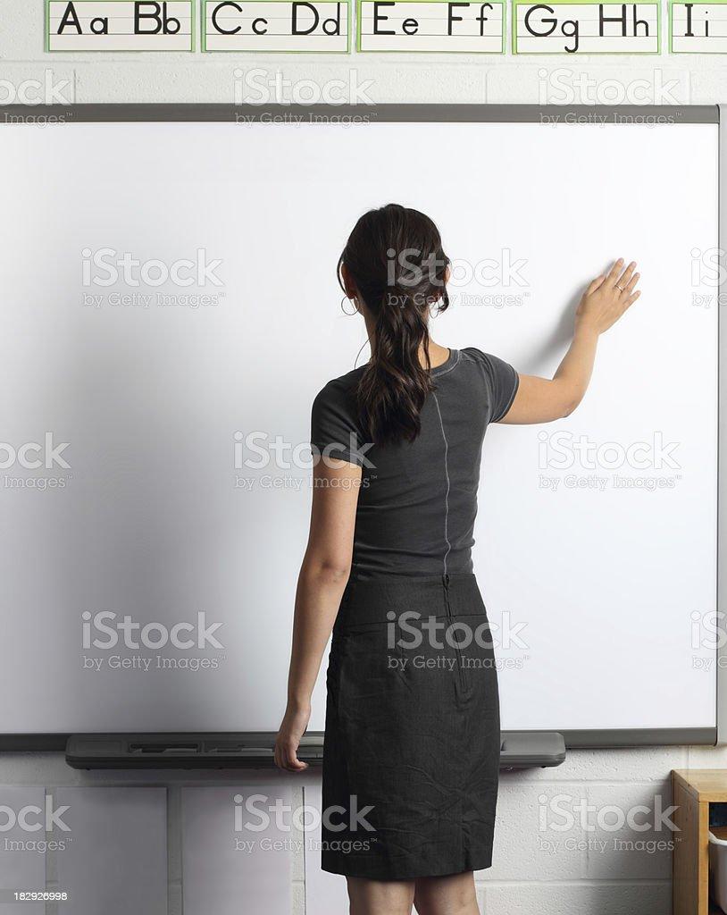 Teacher demonstrates on interactive board stock photo