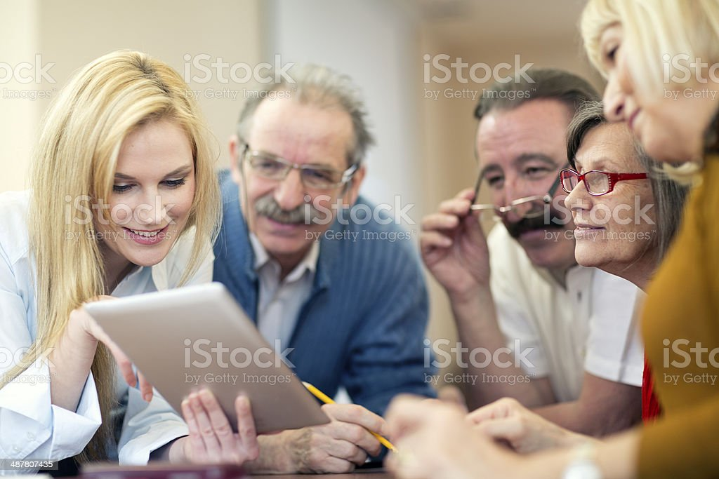 teacher demonstrates  use of digital tablet to seniors group stock photo