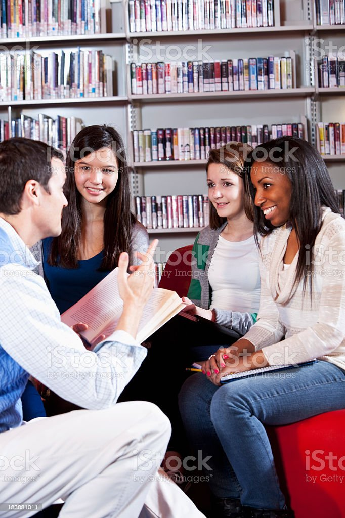Teacher discussing book with teenage students royalty-free stock photo